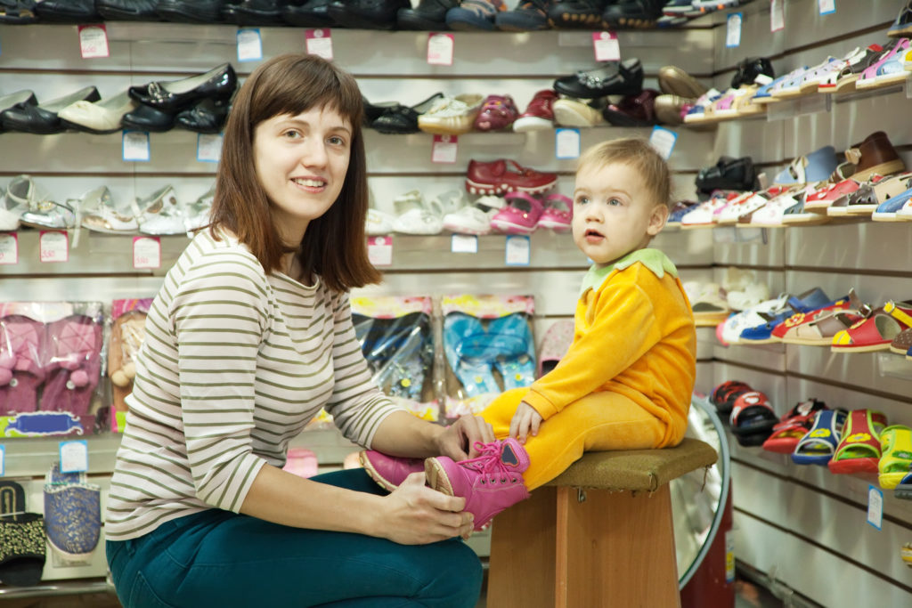Photo of woman with child chooses baby shoes